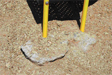Photo showing fall material kicked away from base of play structure.