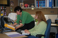 Ergonomics specialist adjusts workstation equipment for employee.