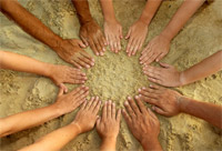 Photo of many people's hands creating a circle in the sand